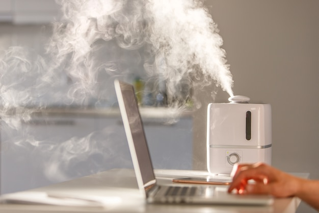 Mann, der am laptop nahe dem aromaöldiffusor auf dem tisch arbeitet, dampf vom luftbefeuchter, weichzeichner
