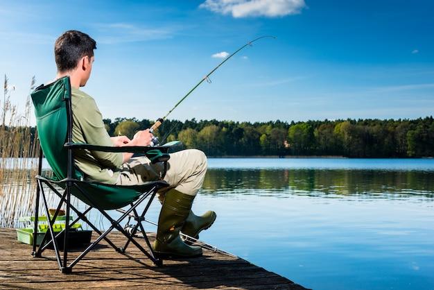 Mann, der am see fischt, der auf steg sitzt