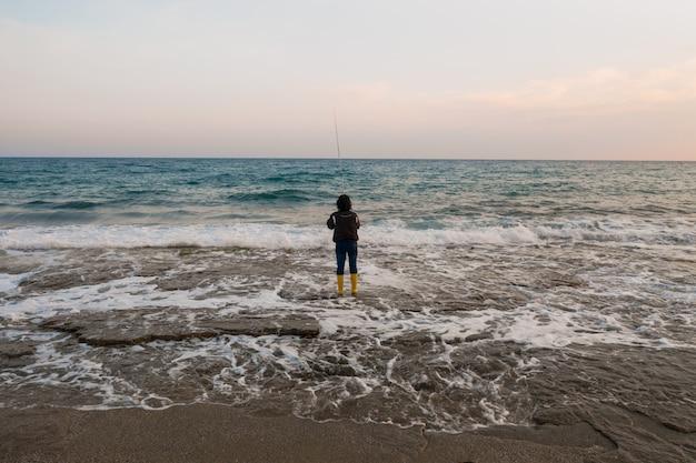 Mann, der am seeufer fischt