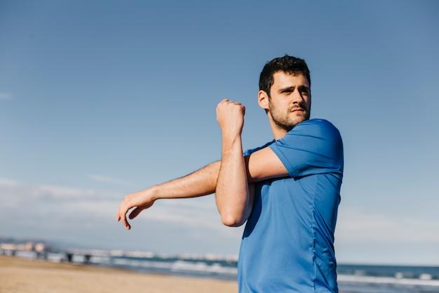 Mann, der am strand ausdehnt