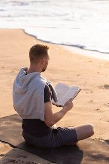 Mann, der am strand liest und meditiert