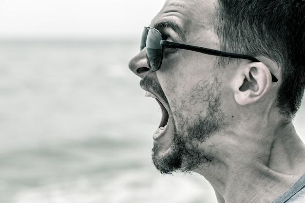 Mann, der am strand schreit