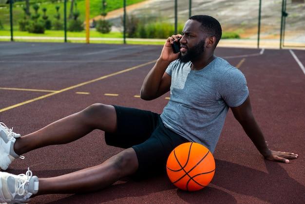 Mann, der am telefon auf basketballplatz spricht