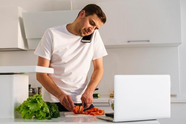 Mann, der am telefon beim kochen spricht