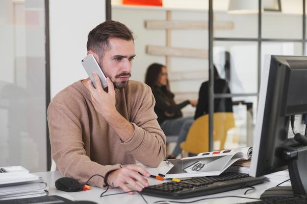 Mann, der am telefon im büro spricht