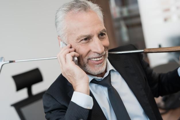 Mann, der am telefon im büro spricht.