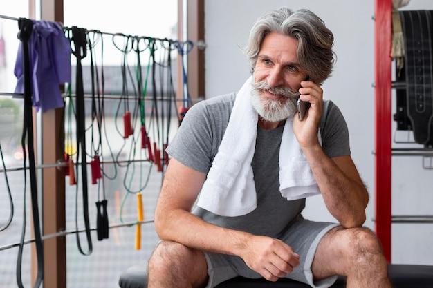 Mann, der am telefon im fitnessstudio spricht