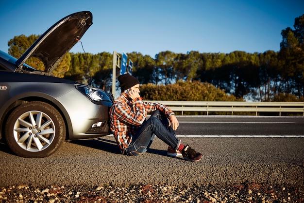Mann, der am telefon neben auto spricht