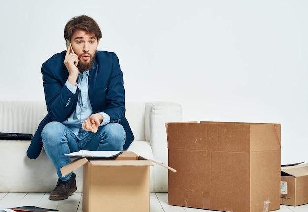 Mann, der am telefon spricht, das auf den couchboxen mit sich bewegenden dingen sitzt, die auspacken. hochwertiges foto