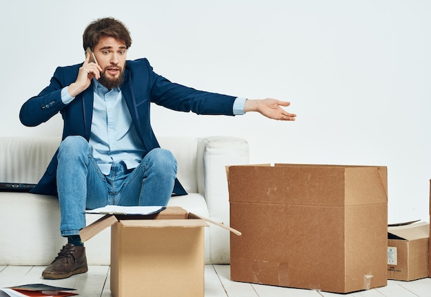 Mann, der am telefon spricht, das auf den couchboxen mit sich bewegenden dingen sitzt, die auspacken