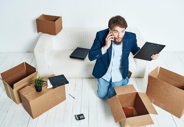 Mann, der am telefon spricht, packt kistenbüroarbeitsplatz-geschäftsmann aus