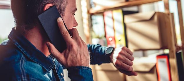 Mann, der am telefon spricht und armbanduhr betrachtet