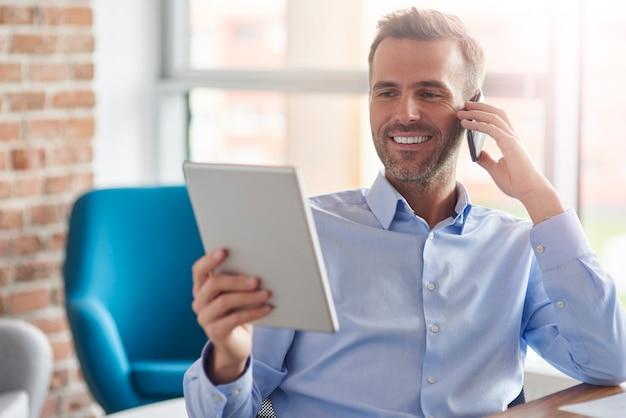 Mann, der am telefon spricht und digitales tablett durchsucht