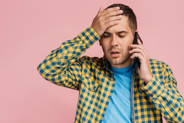 Mann, der am telefon spricht und schlechte nachrichten erhält
