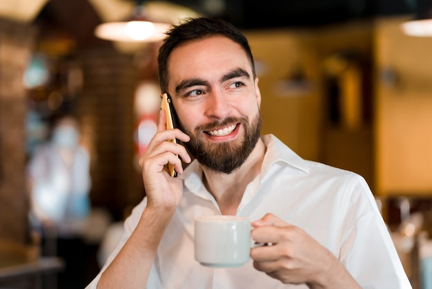 Mann, der am telefon spricht, während er eine tasse kaffee in einem café trinkt.