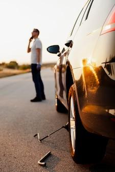 Mann, der am telefon über ein autoproblem spricht