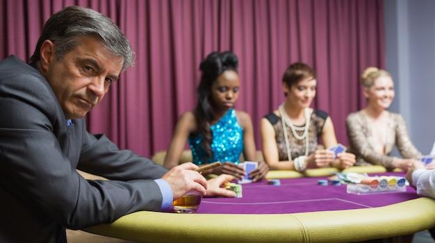 Mann, der am tisch im kasino sitzt