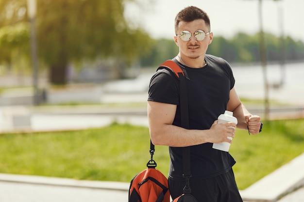 Mann, der am wasser steht. mann in sportkleidung. männchen in einem sommerpark mit rucksack