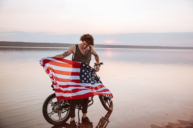 Mann, der amerikanische flagge an der wüste hält, die nahe motorrad steht