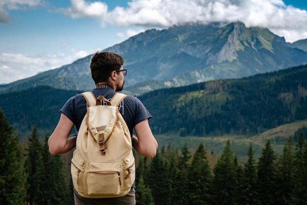 Mann, der an bergen mit schwerem rucksack wandert