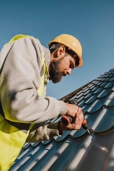Mann, der an dach mit einer niedrigen ansicht des bohrers arbeitet