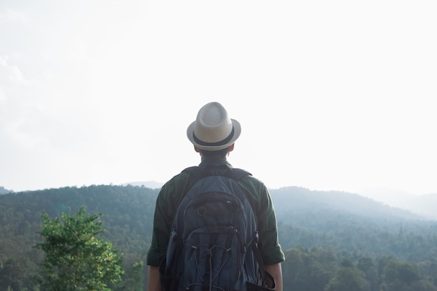 Mann, der an den sonnenuntergangbergen mit schwerem rucksack wandert