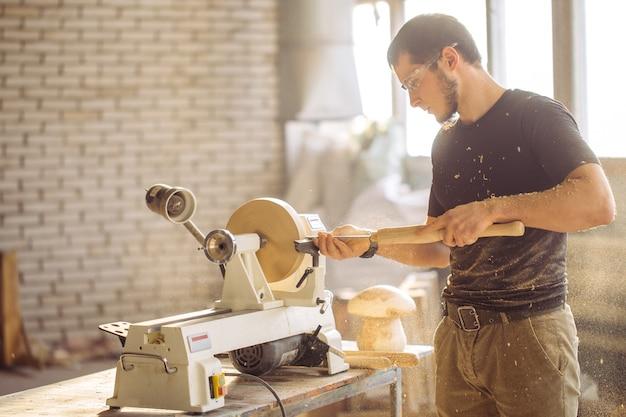 Mann, der an der kleinen holzdrehmaschine arbeitet, ein handwerker schnitzt stück holz