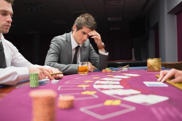 Mann, der an der tabellenhand auf seinem gesicht sitzt