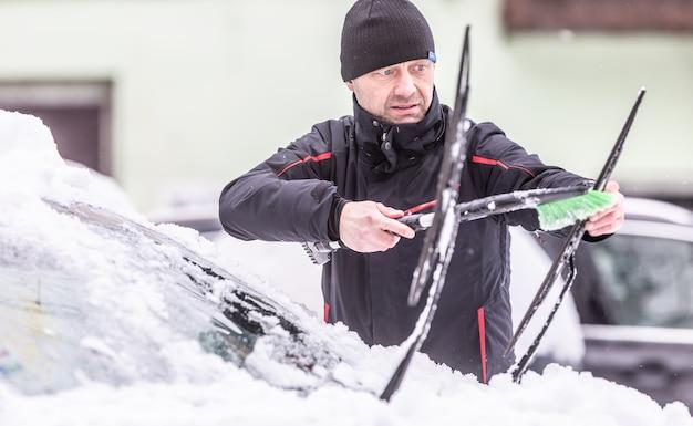 Mann, der an einem frostigen wintertag scheibenwischer putzt, bevor er die fahrt beginnt.