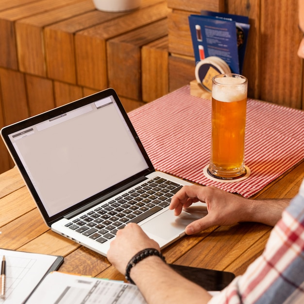 Mann, der an einem laptop mit biergetränk arbeitet