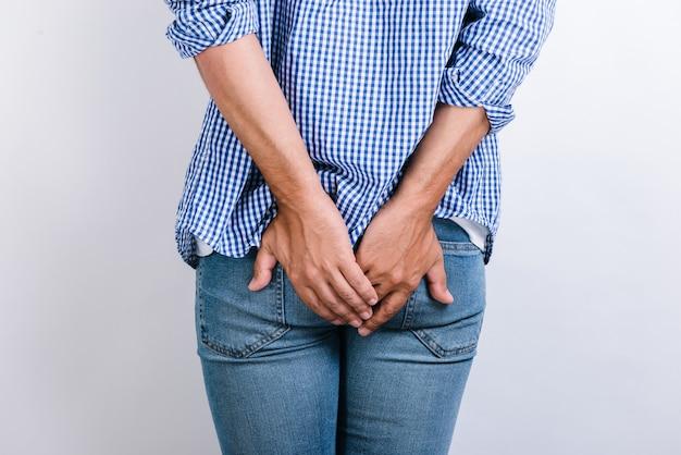 Mann, der an hämorrhoiden und analen schmerzen leidet, während er auf weißem hintergrund posiert. mann, der seine hände auf die schmerzende stelle legt. stock foto