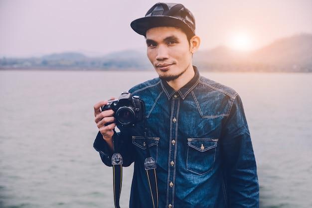 Mann, der an hand kamera an der flussweinlese hält