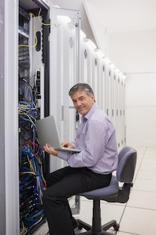 Mann, der an laptop arbeitet, um server zu überprüfen