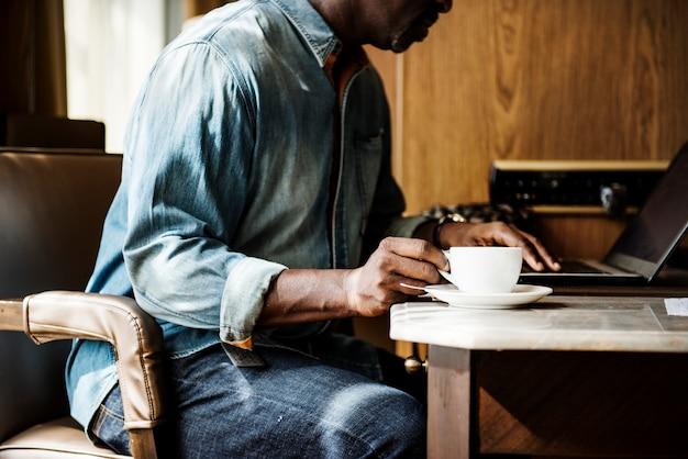 Mann, der an laptop arbeitet und ein heißes getränk isst