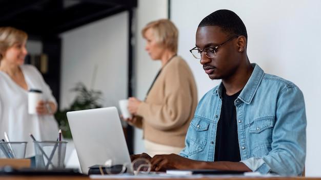 Mann, der an laptop drinnen arbeitet