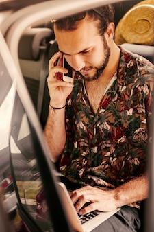 Mann, der an laptop im auto verhandelt und arbeitet