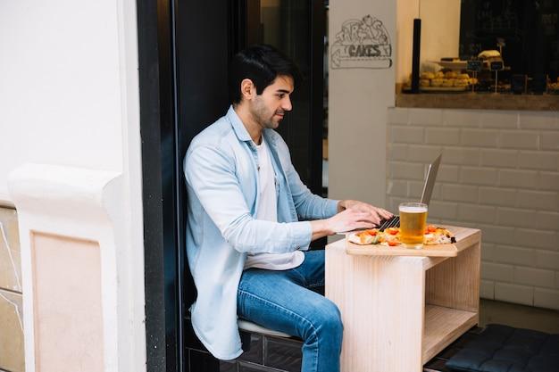 Mann, der an laptop im café arbeitet