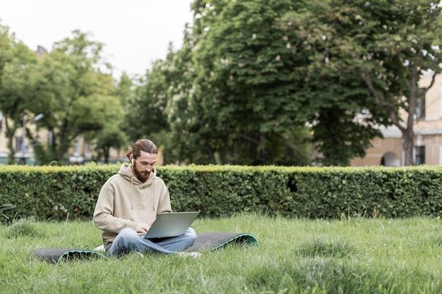 Mann, der an laptop im stadtpark arbeitet