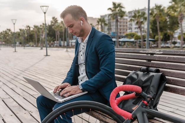 Mann, der an laptop neben seinem fahrrad draußen arbeitet