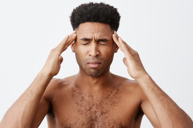 Mann, der an migräne leidet, schläft nur für einige stunden und bereitet sich auf abschlussprüfungen in der universität vor. junger mann, der ohne kleidung vor dem spiegel steht und morgens mit den händen den kopf drückt.