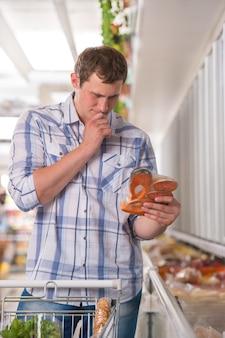 Mann, der an produkte im supermarkt denkt