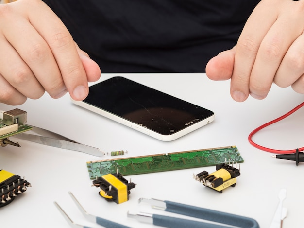 Mann, der an seinem arbeitstisch mit elektronik sitzt