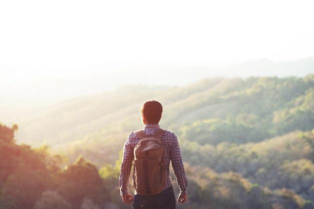 Mann, der an sonnenuntergangsbergen mit schwerem rucksack reist lebensstil fernweh-abenteuerkonzept sommer