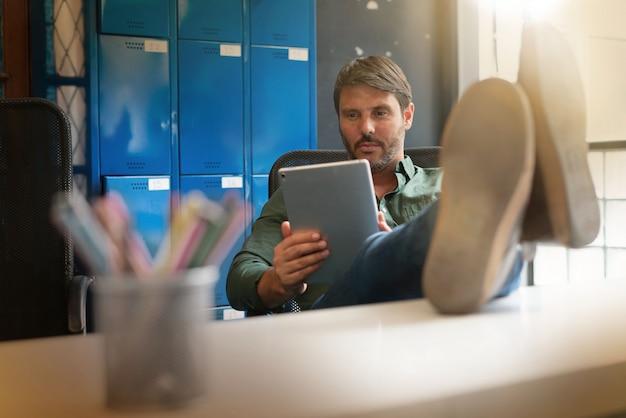 Mann, der an tablette in den modernen büroräumen arbeitet