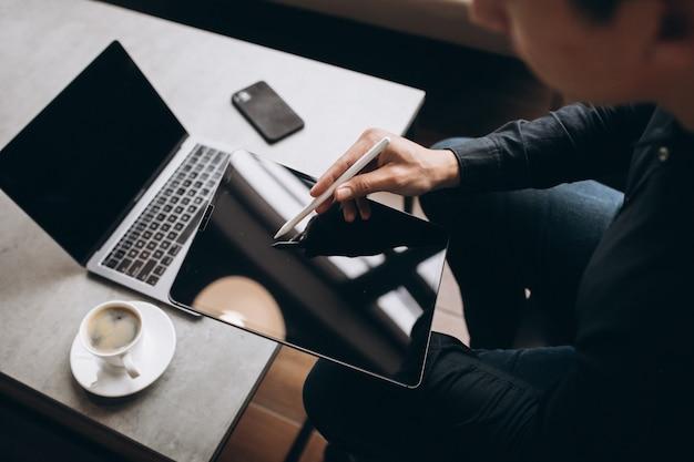Mann, der an tablette nah oben am tisch arbeitet