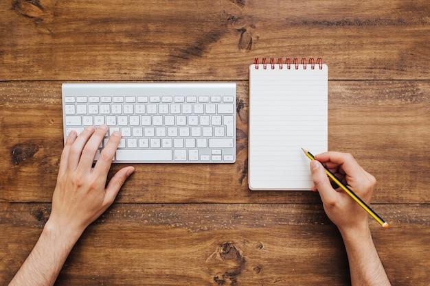 Mann, der an tastatur arbeitet und auf notizblock schreibt.