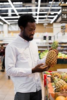 Mann, der ananas im gemischtwarenladen kontrolliert