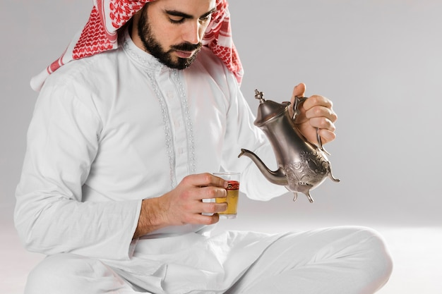 Mann, der arabischen tee in der schale sitzt und gießt