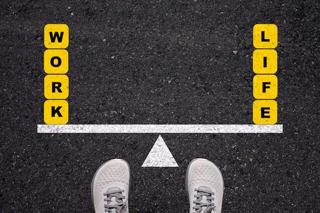Mann, der auf asphaltstraße steht, um zwischen arbeit und leben auf wippe zu balancieren.
