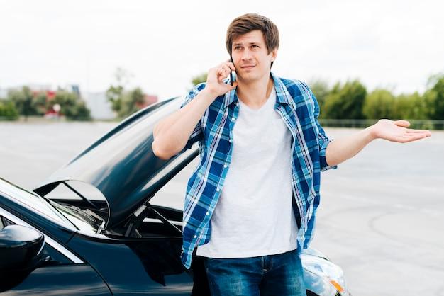 Mann, der auf auto sitzt und am telefon spricht